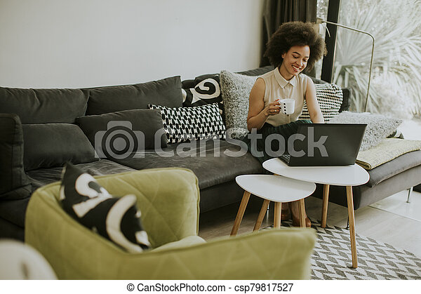 Young beautiful lady with curly hair work on the notebook while sit down on the couch at home - csp79817527