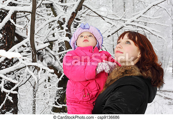 Young beautiful mother with little daughter look up in woods in snow at winter - csp9136686