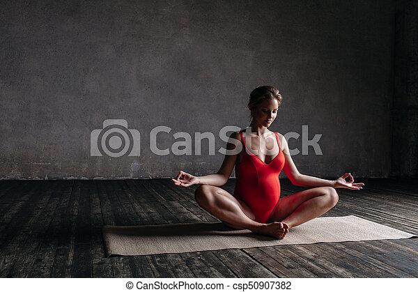 Young beautiful  pregnant yoga posing in studio - csp50907382
