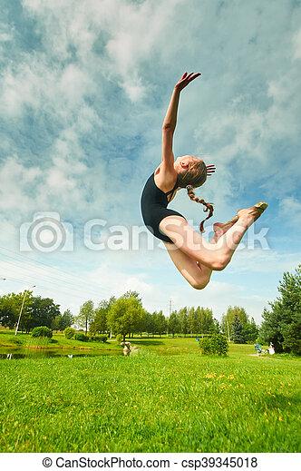 Young beautiful preteen girl doing gymnastics outdoors - csp39345018