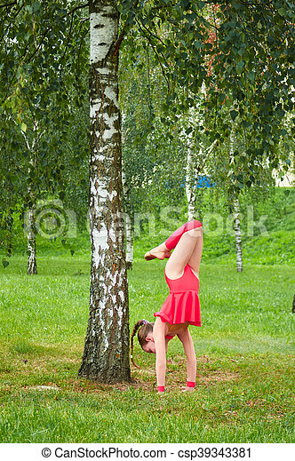 Young beautiful preteen girl doing gymnastics outdoors - csp39343381