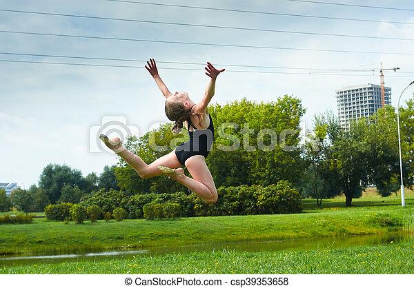 Young beautiful preteen girl doing gymnastics outdoors - csp39353658