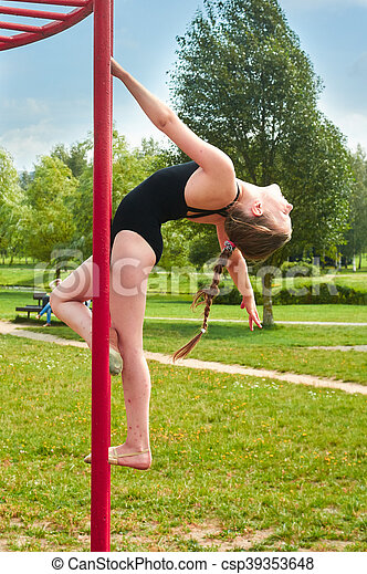 Young beautiful preteen girl doing gymnastics outdoors - csp39353648