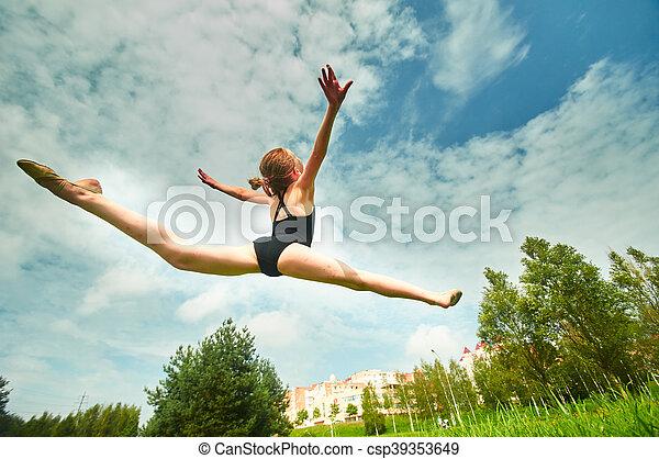 Young beautiful preteen girl doing gymnastics outdoors - csp39353649