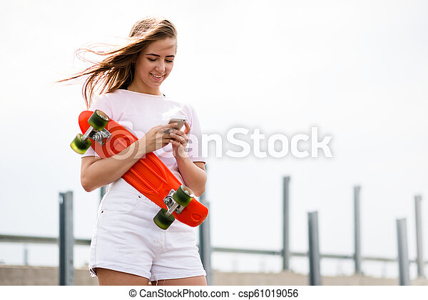 Young Beautiful Smiling Blonde Girl Using Smartphone while Sitting on the Skateboard - csp61019056