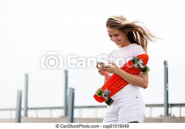 Young Beautiful Smiling Blonde Girl Using Smartphone while Sitting on the Skateboard - csp61019049