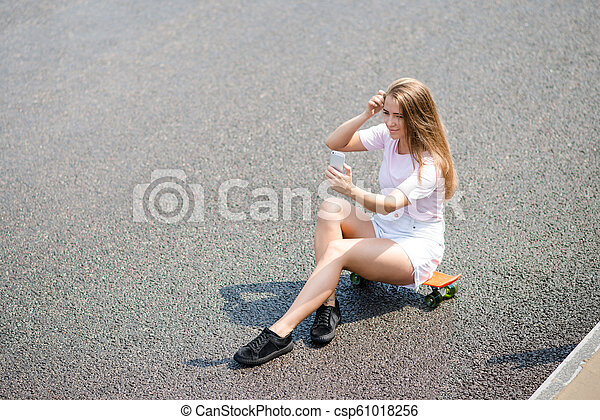 Young Beautiful Smiling Girl Making Selfie with Smartphone while Sitting on the Skateboard on the Road - csp61018256