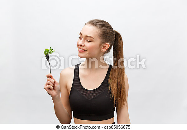 Young beautiful sport woman eating salad on white background. - csp65056675