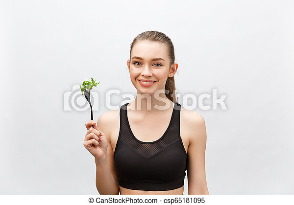 Young beautiful sport woman eating salad on white background. - csp65181095