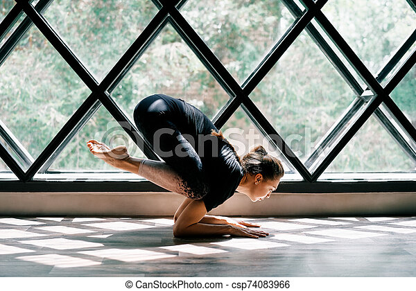 young beautiful woman doing yoga asana baby crow pose on