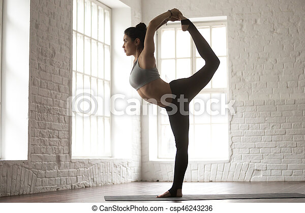 young beautiful woman in natarajasana pose white loft