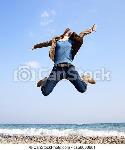 Young beautiful woman jumping at the beach. - csp6050981