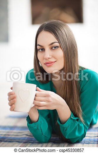 Young beautiful woman lying on plaid with cup of coffee in home - csp45330857