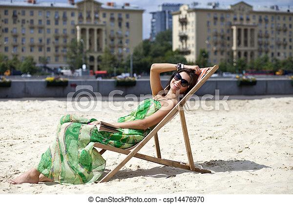 Young beautiful woman relaxing lying on a sun lounger - csp14476970