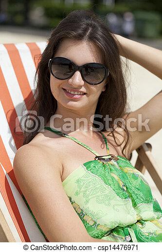 Young beautiful woman relaxing lying on a sun lounger - csp14476971
