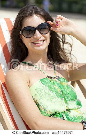 Young beautiful woman relaxing lying on a sun lounger - csp14476974