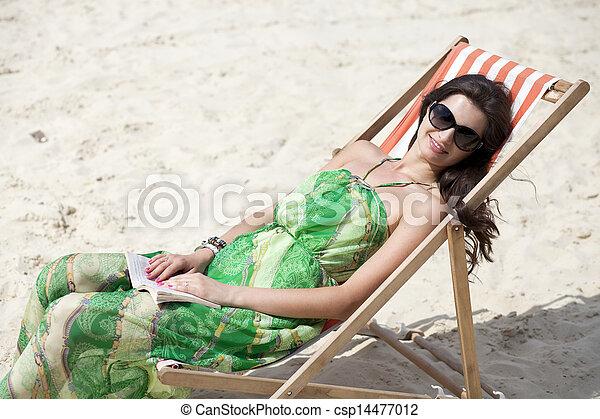 Young beautiful woman relaxing lying on a sun lounger - csp14477012