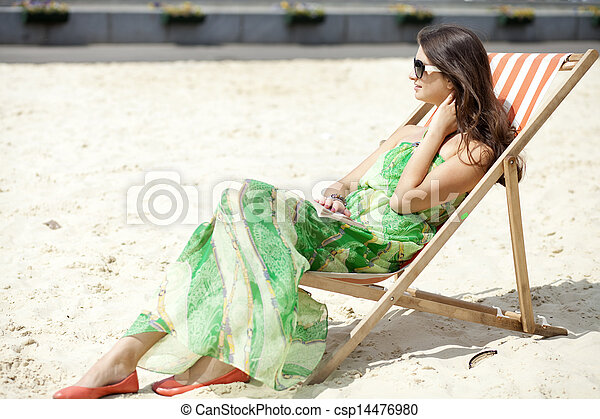 Young beautiful woman relaxing lying on a sun lounger - csp14476980