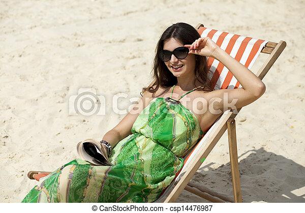 Young beautiful woman relaxing lying on a sun lounger - csp14476987