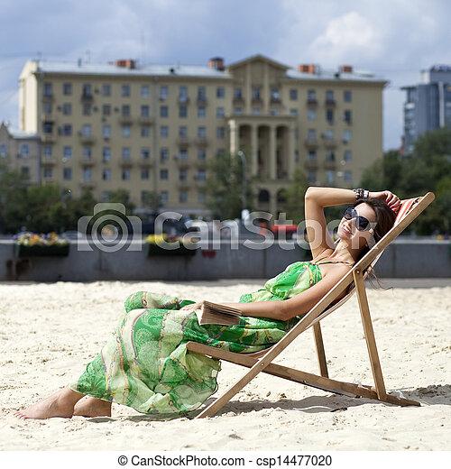 Young beautiful woman relaxing lying on a sun lounger - csp14477020