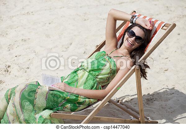 Young beautiful woman relaxing lying on a sun lounger - csp14477040