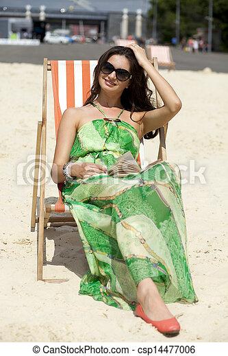 Young beautiful woman relaxing lying on a sun lounger - csp14477006