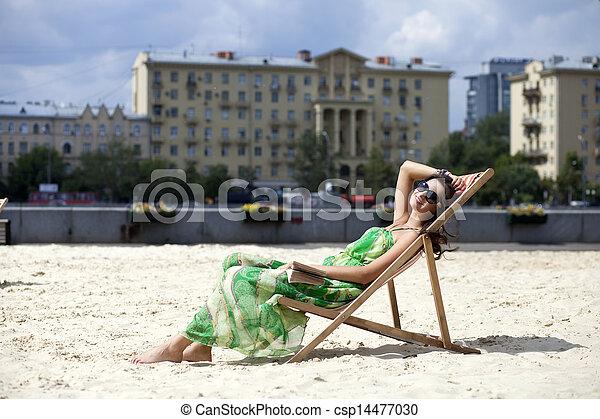 Young beautiful woman relaxing lying on a sun lounger - csp14477030