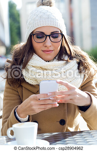 Young beautiful woman using her mobile phone in a cafe. - csp28904962