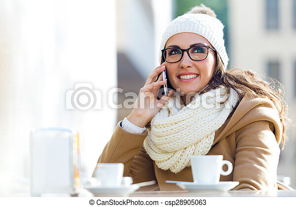 Young beautiful woman using her mobile phone in a cafe. - csp28905063