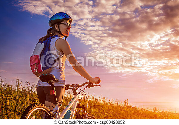 Young bicyclist riding in the field - csp60428052