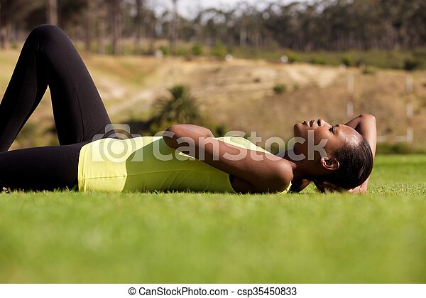 Young black sports woman lying down on grass - csp35450833