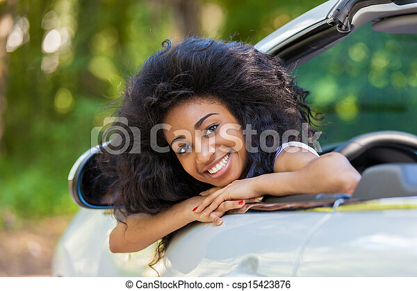 Young black teenage driver seated in her new convertible car - African people - csp15423876