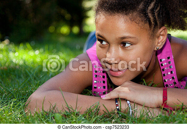 Young black teenage girl lying on the grass - csp7523233