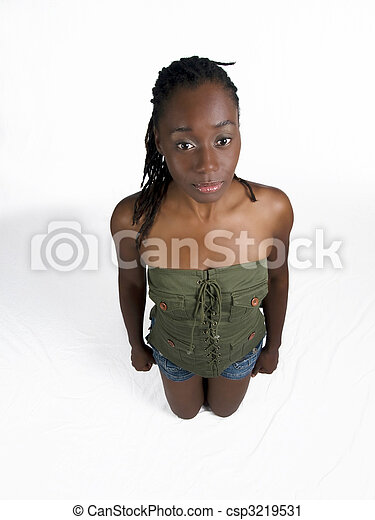 Young black woman kneeling in shorts and green top - csp3219531
