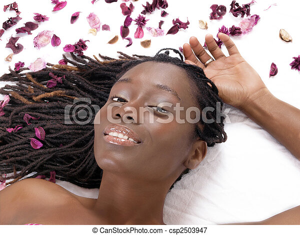 Young black woman reclining on sheet with flower petals - csp2503947