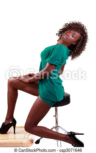 Young black woman sitting in green dress - csp3071646