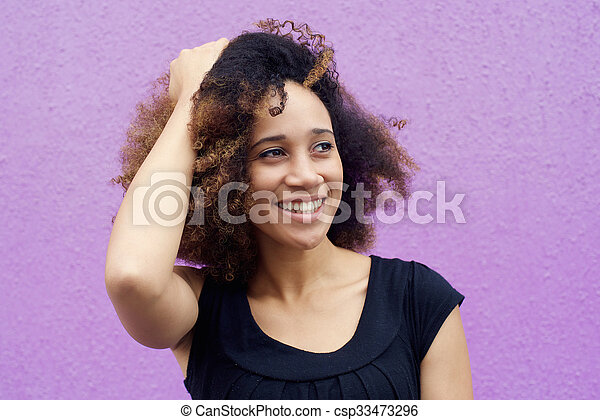 Young black woman smiling with hand in hair - csp33473296