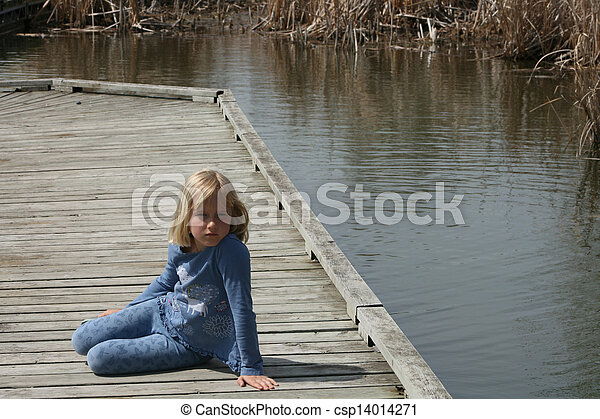 Young Blond Girl Sitting on a Dock - csp14014271