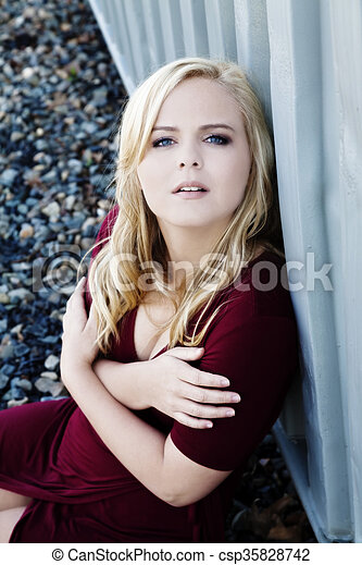 Young Blond Woman Sitting Red Dress Outdoors - csp35828742
