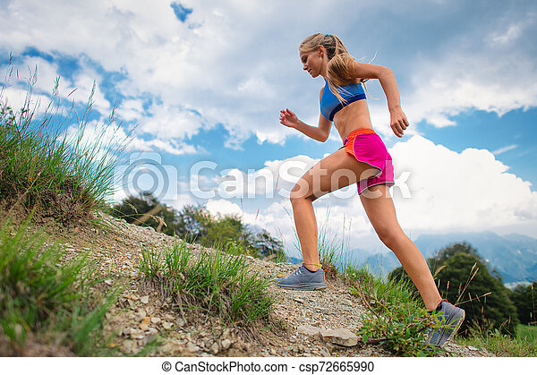 Young blonde girl athlete running in the mountains uphill on trail - csp72665990