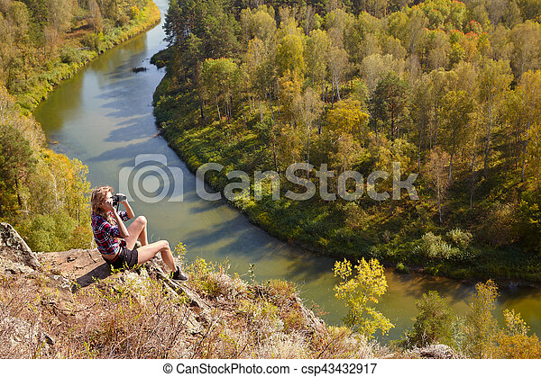 Young blonde woman tourist on a cliff looking through binoculars on the autumn landscape with the river Berd - csp43432917