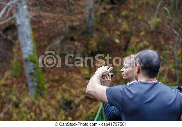 Young blonde woman tourist on a cliff looking through binoculars on the autumn landscape. - csp41737561