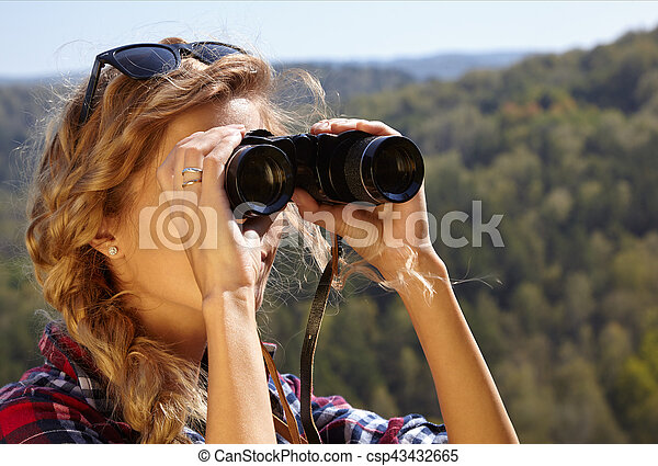 Young blonde woman tourist on a cliff looking through binoculars on the autumn landscape - csp43432665