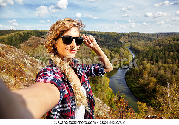 Young blonde woman tourist on a cliff taking selfie picture on background of autumn landscape with the river Berd - csp43432762