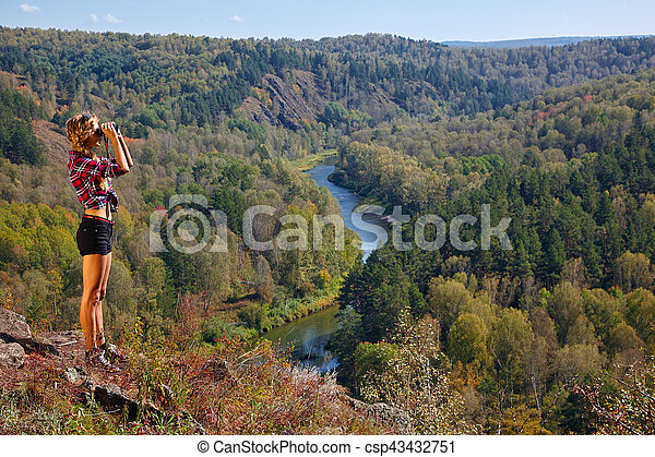 Young blonde woman tourist on a cliff looking through binoculars on the autumn landscape with the river Berd - csp43432751