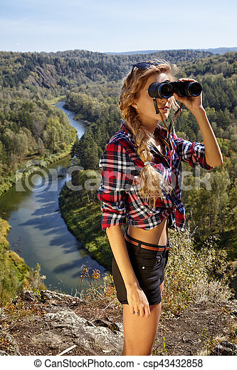 Young blonde woman tourist on a cliff looking through binoculars on the autumn landscape with the river Berd - csp43432858