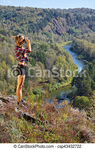 Young blonde woman tourist on a cliff looking through binoculars on the autumn landscape with the river Berd - csp43432722