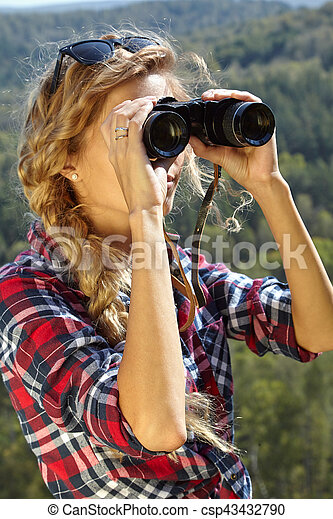 Young blonde woman tourist on a cliff looking through binoculars on the autumn landscape - csp43432790