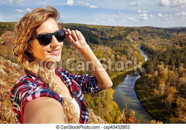 Young blonde woman tourist on a cliff taking selfie picture on background of autumn landscape with the river Berd - csp43432803
