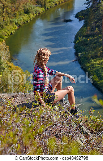 Young blonde woman tourist sit on a cliff on background of siberian autumn landscape with the river Berd - csp43432798